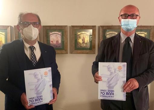 Il libro 1950-2020 70 anni di Rotary ad Asti nella mani del dirigente rotariano Giorgio Gianuzzi (a sinistra) autore del libro e Marco Stobbione presidente del Rotary Club di Asti.