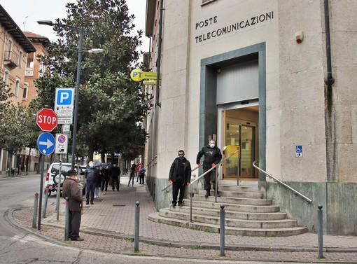 """Nella foto, scattata il 27 marzo, una delle prime giornate di consegna delle pensioni """"scaglionate"""", file ordinate di fronte alle Poste centrali di corso Dante"""