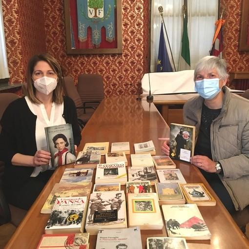 """Il sindaco Anna Macchia e la volontaria della biblioteca Luciana Arduino con i libri di """"Pagine di libertà""""."""